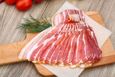 Photo for Fresh cold sliced bacon with dill branch on the wood background - Royalty Free Image