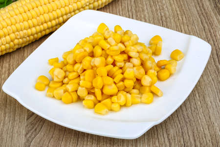 Foto de Canned sweet corn in the bowl on wood background - Imagen libre de derechos