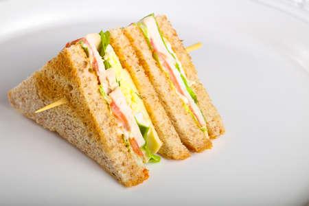 Foto de Club sandwich with meat, cheese and vegetables - Imagen libre de derechos