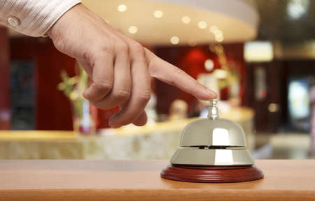 Hand of a man using a hotel bell