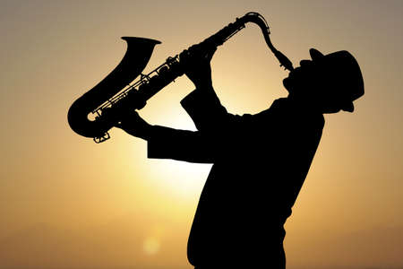 Photo for Saxophonist. Man playing on saxophone against the background of sunset  - Royalty Free Image
