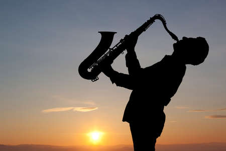 Photo for Man playing on saxophone against the background of sunset - Royalty Free Image