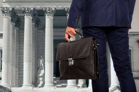 Photo for The lawyer with a briefcase is on against the courthouse - Royalty Free Image