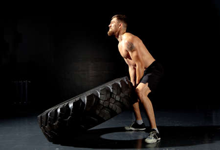 Photo for Crossfit training. Muscular young man flipping tire at gym - Royalty Free Image