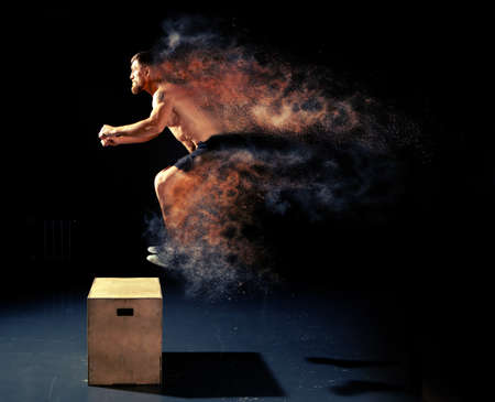 Photo pour Man jumping on fit box in gym. Male with torso exercises jump on the dark background. - image libre de droit