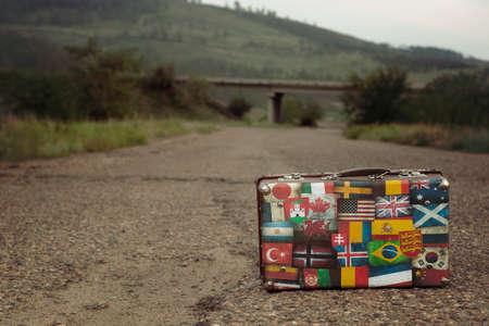 Foto de Vintage brown threadbare suitcase with collection of retro travel flag labels - Imagen libre de derechos