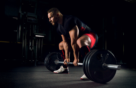 Photo pour Athlete in the gym is prepared to perform an exercise called deadlift - image libre de droit
