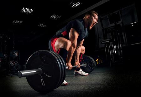 Foto de Athlete screams in the gym to motivate himself to perform an exercise called deadlift - Imagen libre de derechos