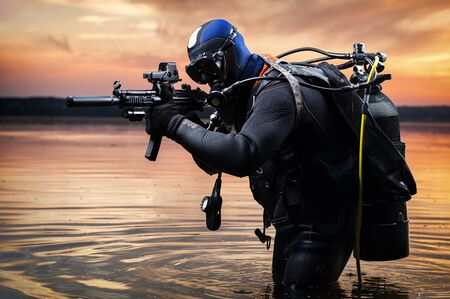 Foto de The marine comes out of the water and moves toward the target with weapons in hand. The concept of video games, advertising, instability in the world, country conflicts. Mixed media - Imagen libre de derechos