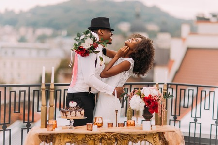Foto de Stylish african wedding couple having fun on the balcony with luxury golden table in oriental style on foreground. - Imagen libre de derechos