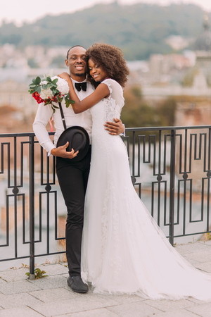 Foto de Happy black bride and groom softly hugging on the terrace with cityscape on background. - Imagen libre de derechos