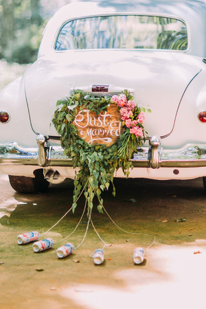 Foto de Vintage wedding car with just married sign and cans attached, close-up. - Imagen libre de derechos