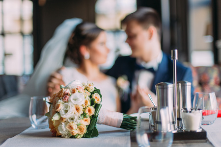 Photo pour Romantic moment of newlywed couple. Stylish young groom and his beautiful bride holding each other. Wedding bouquet laying on served table at foreground - image libre de droit