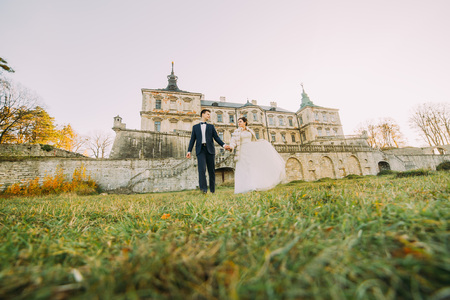 Photo pour The full-length view of the newlyweds holding hands and walking in the yard of the castle. Down view - image libre de droit
