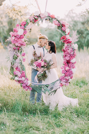 Foto de The close-up portrait of the newlyweds holding the bouquet and standing behind the wedding peonies arch in the sunny forest. - Imagen libre de derechos
