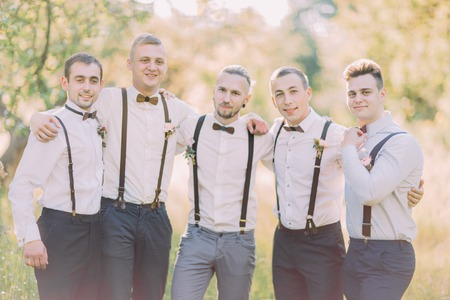 Photo for The horizontal close-up portrait of the modern-dressed grom and his best men at the background og the green summer field. - Royalty Free Image