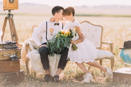 Foto de The lovely close-up horizontal portrait of the newlyweds sitting head-to-head on the sofa. The bride is holding the colourful wedding bouquet at the background of the field. - Imagen libre de derechos