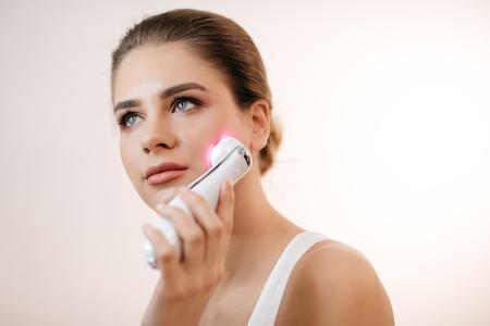 Foto de Young healthy woman with natural make-up using the facial massage machine - Imagen libre de derechos