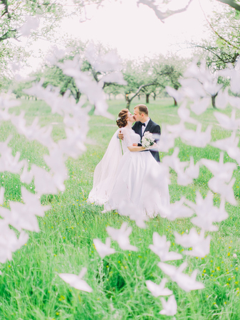 Photo for The happy newlyweds are kissing behind the paper swans in the green forest. - Royalty Free Image