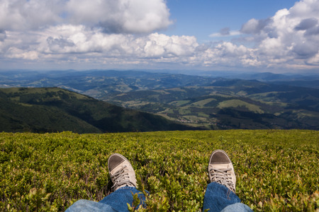 Photo pour Man sitting on a high mountain top with first person perspective view, legs in focus - image libre de droit