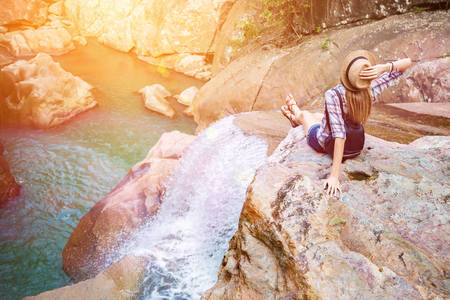 Foto de Happy woman sitting on the rock edge near waterfall enjoying stunning view, filtered with sun flares - Imagen libre de derechos