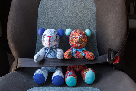 Photo pour Stuffed toys buckled with safety belt in a car - image libre de droit