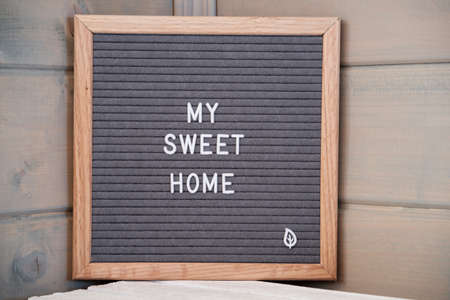 Photo pour Grey lettering Board with felt coating in wooden frame with English text my sweet home in corner of wooden house - image libre de droit