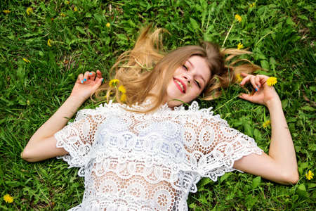 Photo for Cute girl with bliss lying on the green lawn. - Royalty Free Image