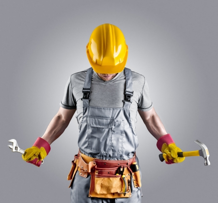 Foto de builder in a helmet with a hammer and a wrench - Imagen libre de derechos