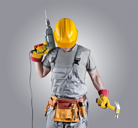 Photo pour builder in a helmet with a hammer and a drill - image libre de droit