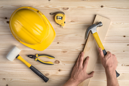 Photo pour tools and hands working with hammer and helmet on wooden background - image libre de droit