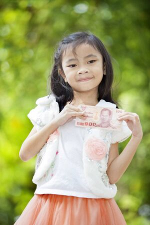 Asia girl with Thai money in green nature background.