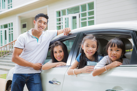 Photo pour Beautiful family portrait smiling outside their new house, just arrive new home by car. - image libre de droit