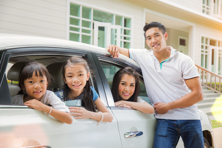Photo for Beautiful family portrait smiling outside their new house, just arrive new home by car. - Royalty Free Image