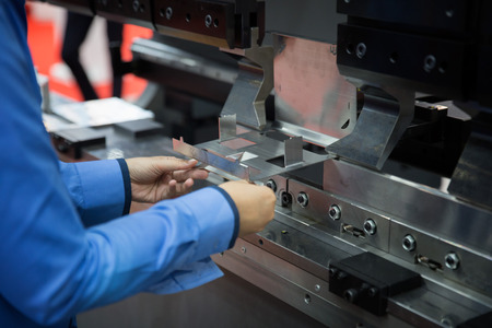 Photo pour operator bending metal sheet by sheet bending machine, production work process in fabricated factory by worker, manual or semi auto processing. - image libre de droit