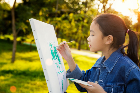 Foto de little painter at work in the park with palette and canvas, butter fly drawing with gild in park wint green outdoor backgroung, kid, teen and student concept. - Imagen libre de derechos