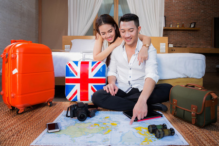 Photo pour Young couple planning honeymoon vacation trip with map from they room in resort. - image libre de droit