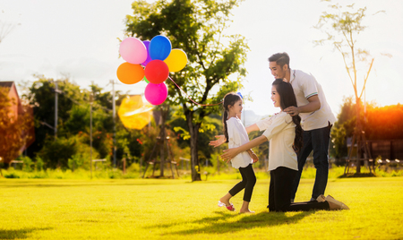 Photo pour Daughter running to mother and father, She enjoyed the play balloons - image libre de droit