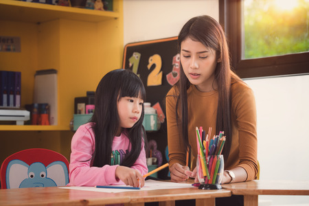 Foto de Teacher and student take home work togather in preschool, Library, mother, art, school, teacher, education and kid concept - Imagen libre de derechos
