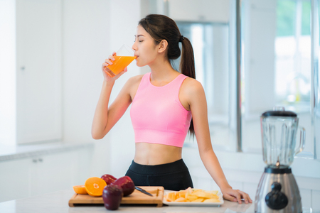 Photo for Asian lady in fitness sport wear drink a mix fruit and vegetable for beauty, slim and health after yoga class - Royalty Free Image