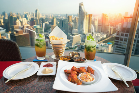 Photo for Food, snacks and mojito cocktail on the deak in rooftop bar in Bangkok city, Thailand - Royalty Free Image