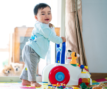 Photo for Asian baby training walking with walker toy. - Royalty Free Image