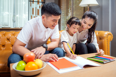 Foto de Asian father, mother and daughter doing home work togather in living room, this immage can use for education, home and family concept - Imagen libre de derechos