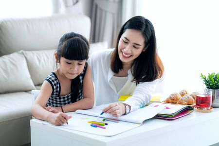 Foto de Mother teach Asian preschool student do homework by drawing by a color, this image can use for girl - Imagen libre de derechos