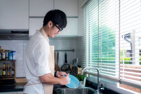 Photo pour Asian man smile and washing a dish in kitchen room, this image can use for husband, worker, job and cleaning concept - image libre de droit