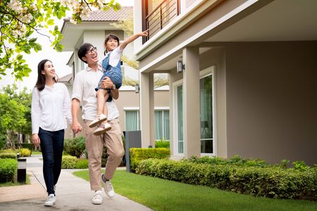 Foto de Beautiful family portrait smiling outside their new house with sunset, this photo canuse for family, fathe, mother and home concept - Imagen libre de derechos