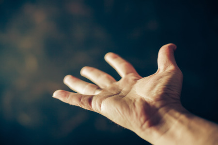 Foto de hands begging on a brown background - Imagen libre de derechos
