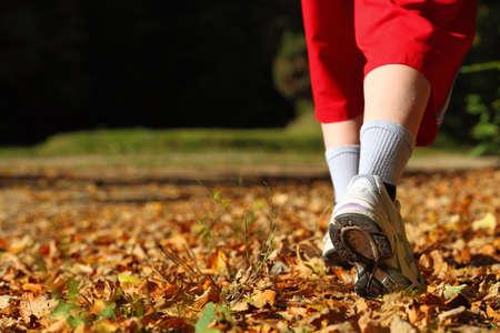 Foto de Woman walking cross country and trail in autumn forest - Imagen libre de derechos