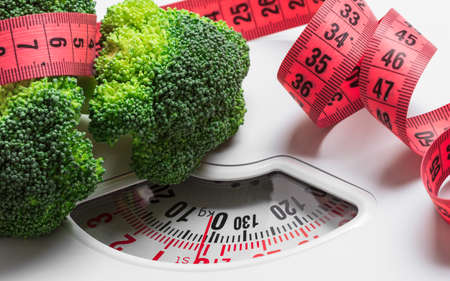 Dieting healthy eating slim down weight control concept. Closeup green broccoli with measuring tape on white scales