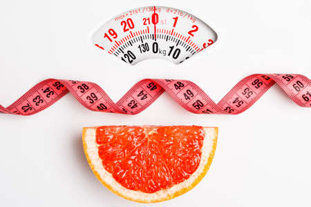 Photo pour Dieting healthy eating slim down concept. Closeup grapefruit slice with measuring tape on white weight scale - image libre de droit